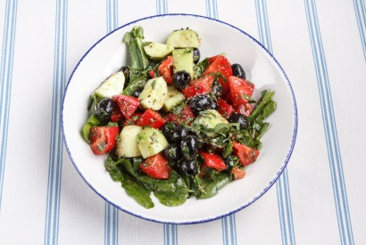 Salad from fresh cucumbers and tomatoes with nut sauce and olives